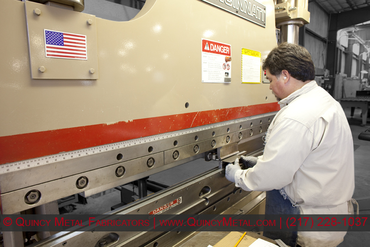 A Quincy Metal employee folds a smaller piece of sheet metal on a 130 ton Cincinnati CNC press brake.